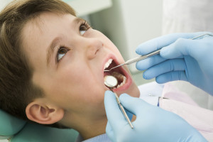 young boy opening his mouth during dental checkup